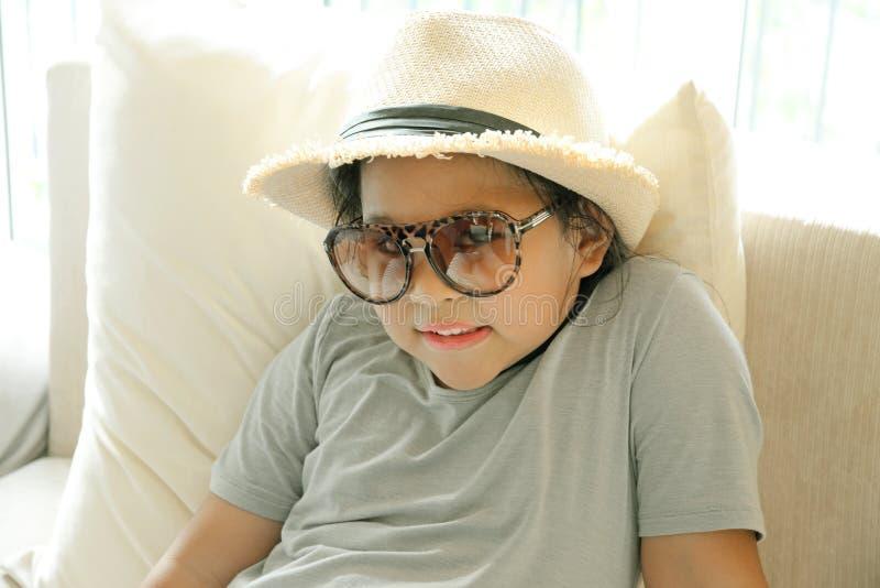 La belle petite fille de sourire en verres s'assied au salon (détendez) photo libre de droits