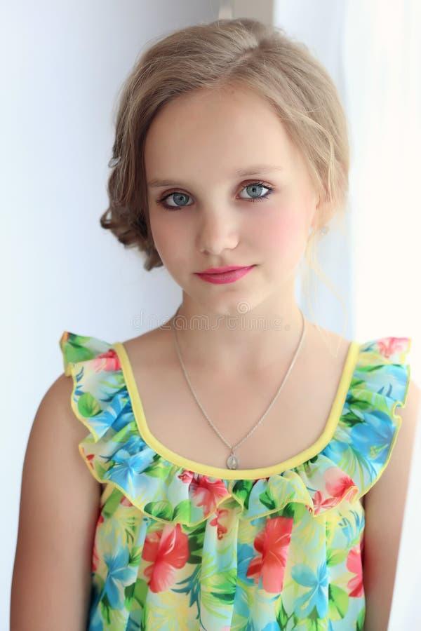La belle petite fille douce avec une coiffure de fête avec les lèvres et les yeux peints est près de la fenêtre image libre de droits