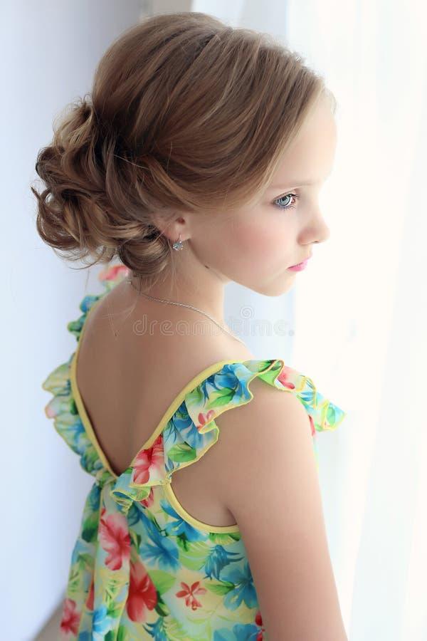 La belle petite fille douce avec une coiffure de fête avec les lèvres et les yeux peints est près de la fenêtre images libres de droits