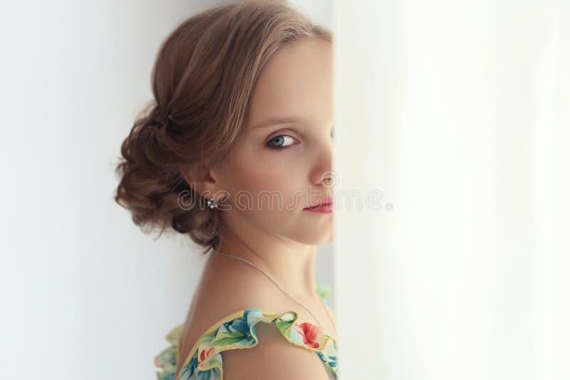 La belle petite fille douce avec une coiffure de fête avec les lèvres et les yeux peints est près de la fenêtre photo libre de droits