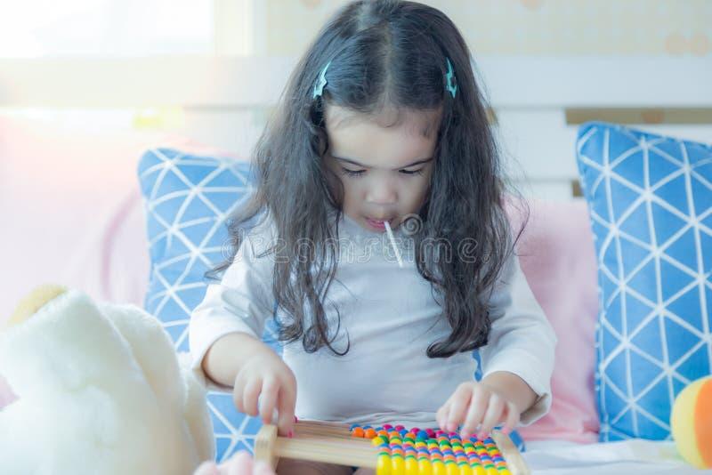 La belle petite fille jouant le jouet sur le lit à la chambre à coucher et la fille d'enfant ou préscolaire mignonne mangent la s image libre de droits