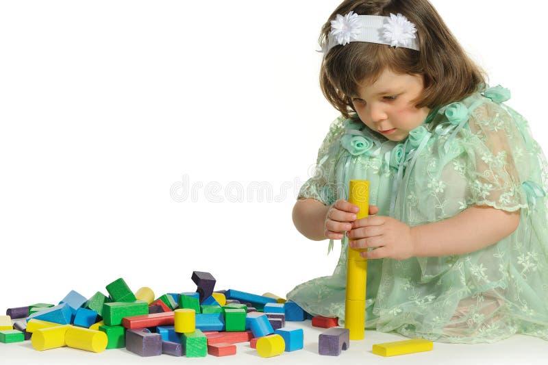 La belle petite fille joue les cubes en bois en couleur photo libre de droits