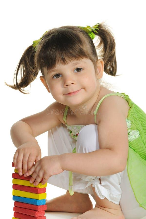 La belle petite fille joue les cubes en bois en couleur photographie stock