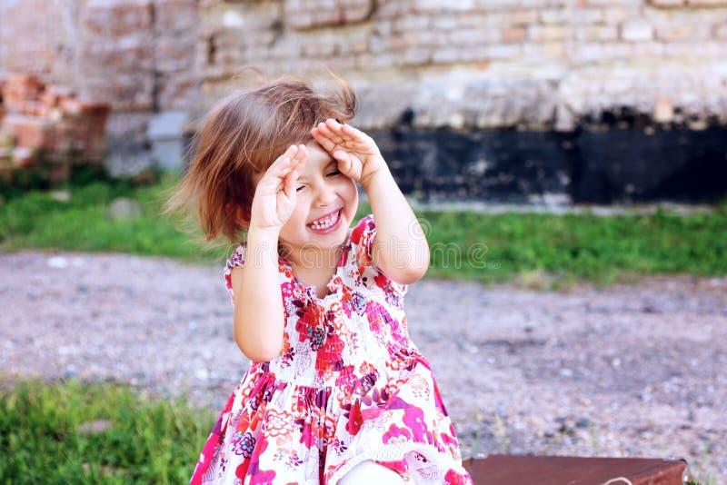 La belle petite fille mignonne cache son visage dans des ses mains images stock