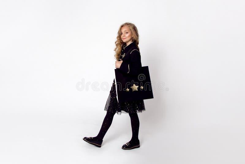 La belle petite fille mignonne habillée dans le costume de Santa Claus va faire des emplettes photographie stock libre de droits