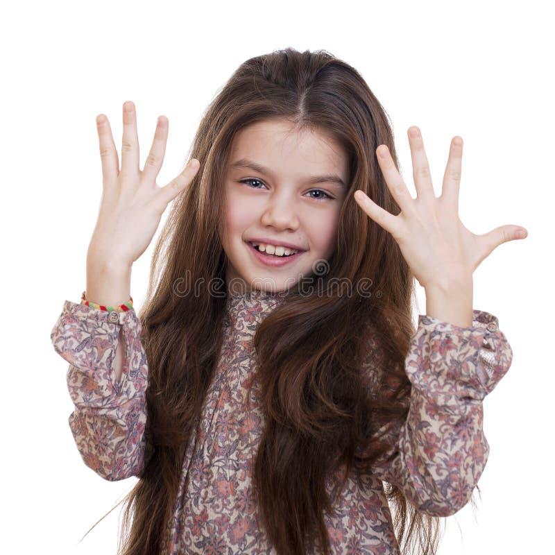 La belle petite fille prouve qu'elle était neuf années photographie stock libre de droits