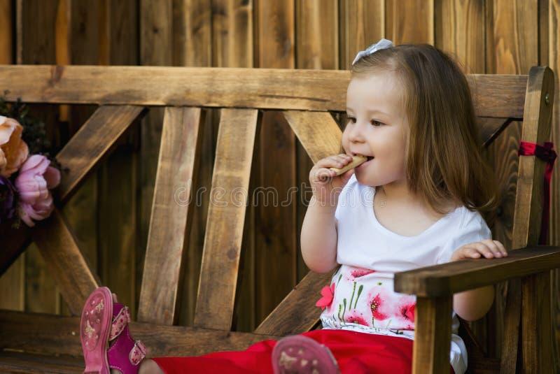 La belle petite fille s'asseyant sur un banc en bois et ont un cooki photographie stock libre de droits
