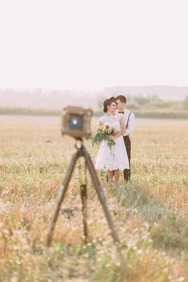 La belle photo des nouveaux mariés étreignant derrière la vue brouillée du vieil appareil-photo de vintage Le marié est étreindre images libres de droits