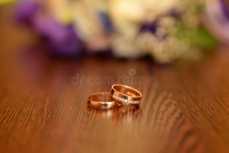La belle photo modifi?e la tonalit? avec des anneaux de mariage se trouvent sur une surface en bois dans la perspective d'un bouq photo stock