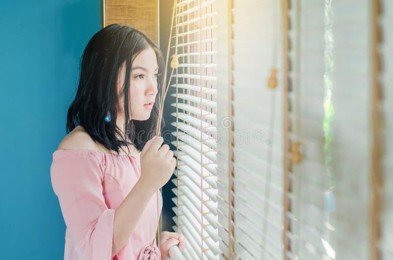 La belle position de femme près de la fenêtre d'intérieur pendant les matins sont très agréable photo libre de droits