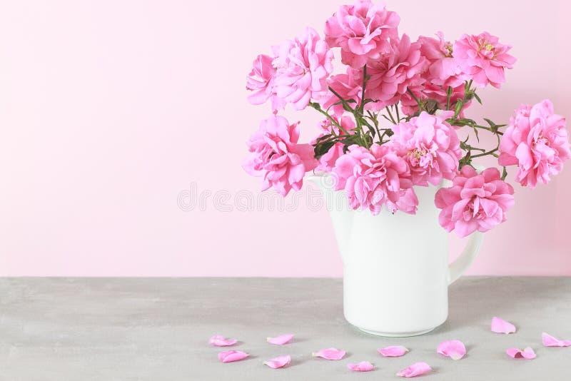 La belle rose de rose fleurit le bouquet dans le vase blanc sur la table grise photos stock