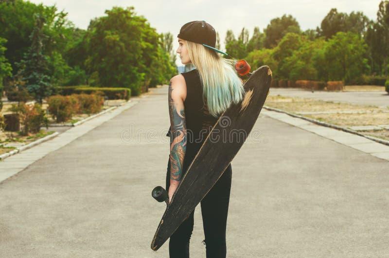 La belle, sexy blonde de hippie avec les cheveux bleus dans le tatouage se tient avec un longboard qu'il est tourné de retour sur images libres de droits