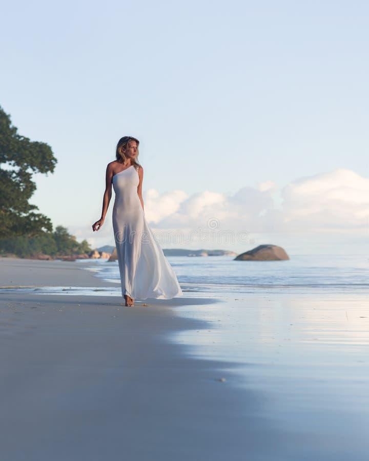 La belle, sexy femme blonde marche à la plage tropicale, longue robe photos libres de droits