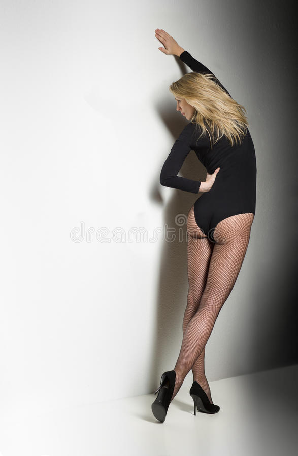 La belle, sexy femme se tient dans le corps noir et les bas photo libre de droits