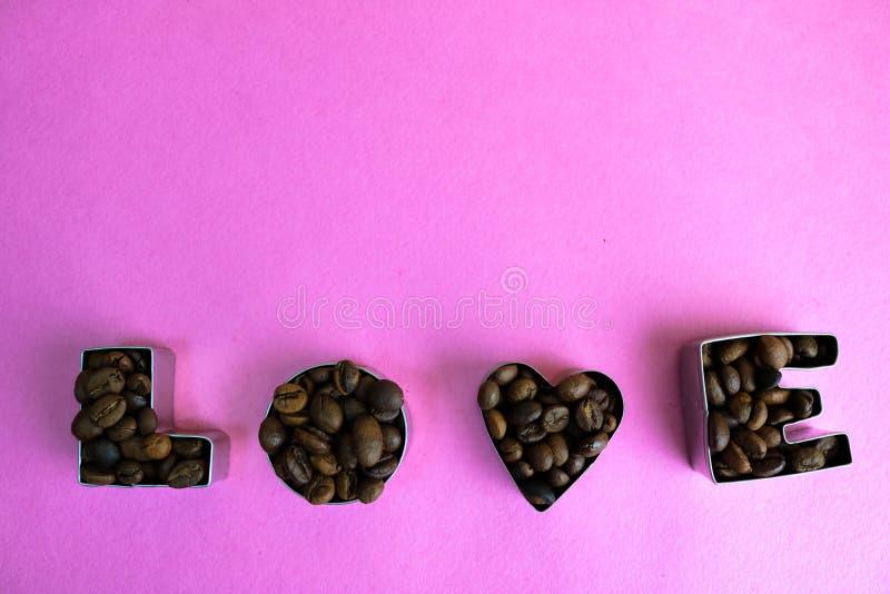 La belle texture avec l'inscription du jour de valentine d'amour de mot faite à partir de rôtir a choisi les grains de café aroma images libres de droits