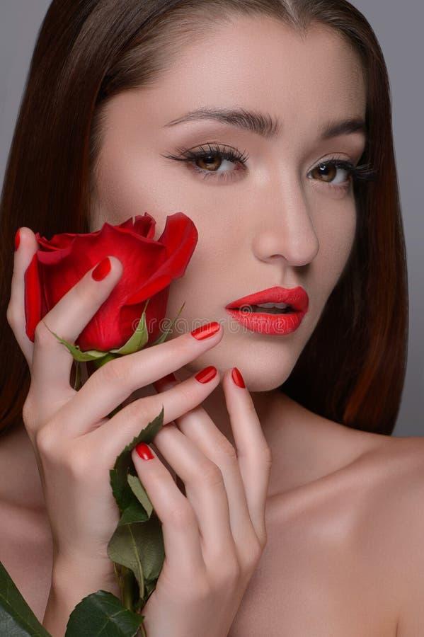 La belleza con subió. Retrato de las mujeres hermosas que sostienen la rosa cerca imagen de archivo libre de regalías