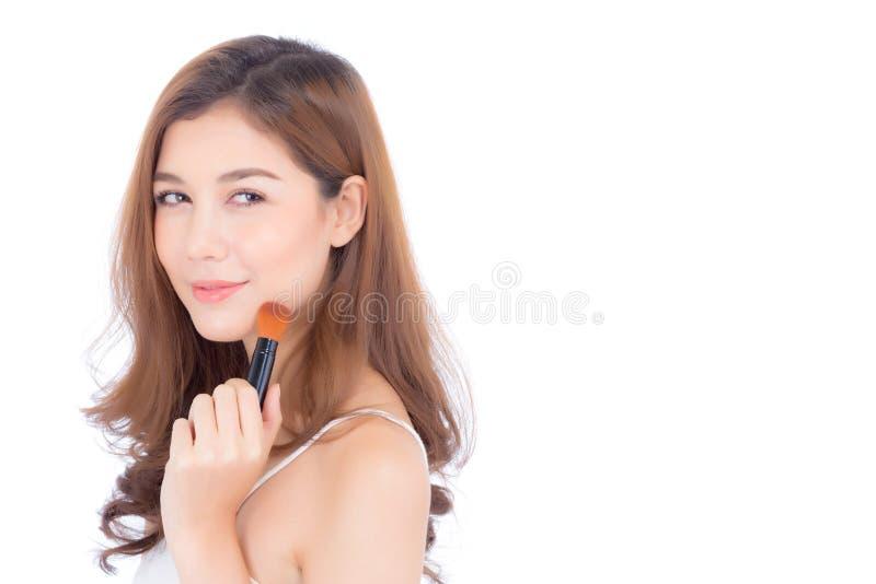 La belleza de la aplicación asiática de la mujer del retrato compone con el cepillo de la mejilla aislado fotos de archivo