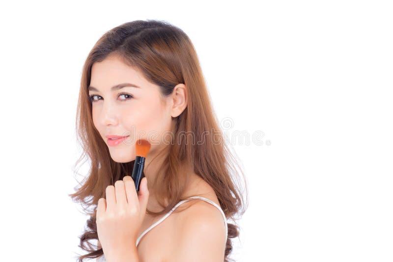 La belleza de la aplicaci?n asi?tica de la mujer del retrato compone con el cepillo de la mejilla aislado en el fondo blanco fotos de archivo