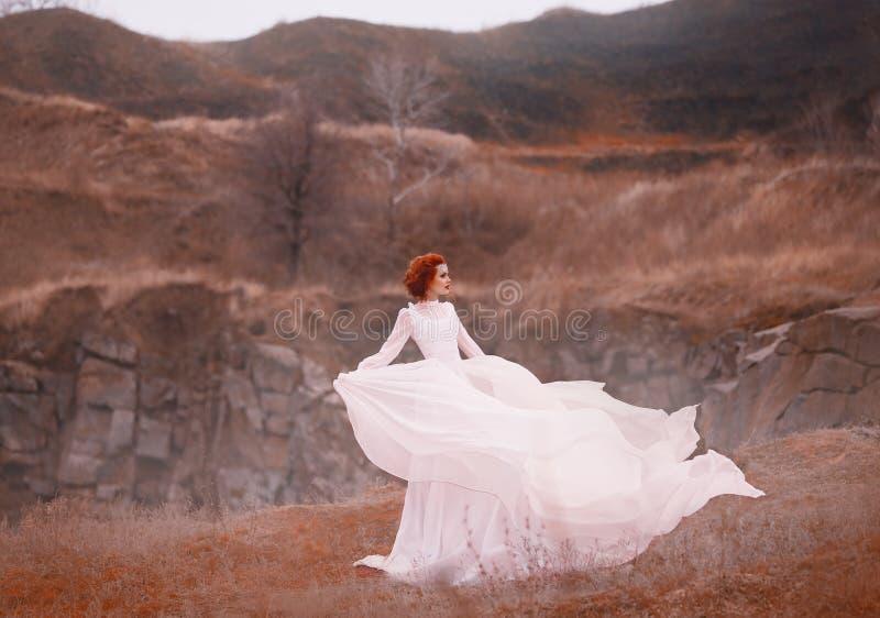 La belleza pelirroja en un vestido blanco del vintage, se coloca encima de una colina, fondo de las montañas rocosas Equipo lujos imagen de archivo