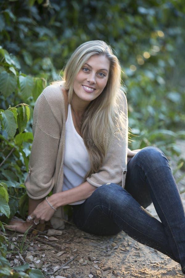 La bellezza australiana con capelli biondi lunghi si siede da un albero immagine stock libera da diritti