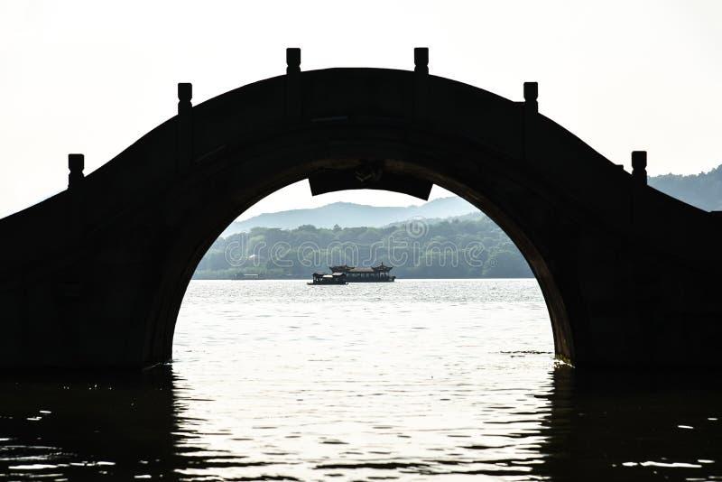 La bellezza del paesaggio del Lago occidentale Xihu, una barca da turismo, un ponte silhouette e un padiglione nella Cina di Hangz immagine stock libera da diritti