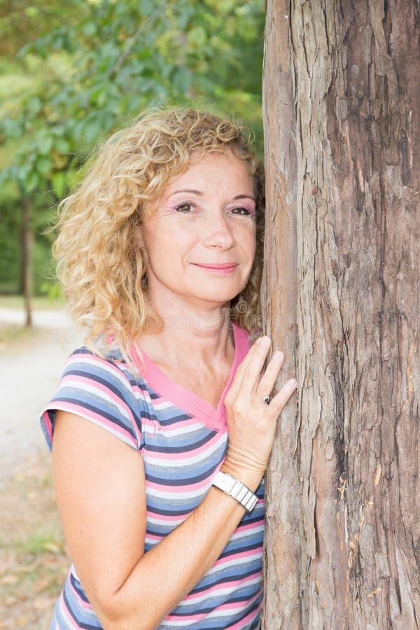 la bellezza senior si è ritirata la donna in parco contro l'albero fotografie stock