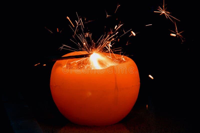 La bengala de la Navidad se enciende de la llama de vela Chispas que estallan en el aire imagen de archivo