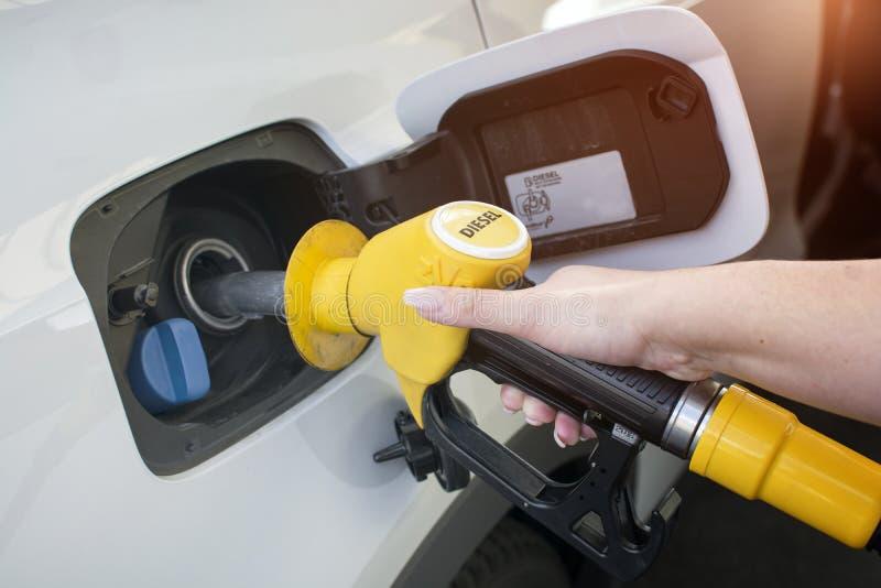 La benzina di riempimento e di pompaggio della mano della donna lubrifica l'automobile con combustibile a He rifornisce di carbur immagini stock