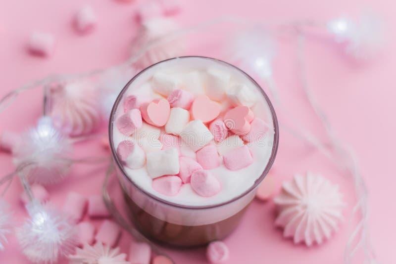 La bevanda calda con crema, le caramelle gommosa e molle ed il cuore montati ha modellato le caramelle di cioccolato immagini stock