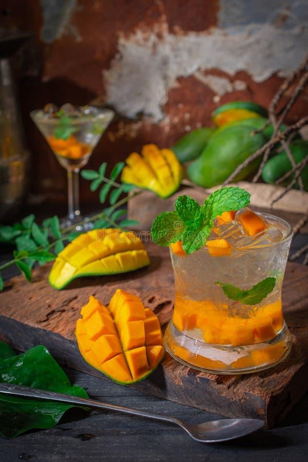 La bevanda fresca della soda del mango del ghiaccio sulla tavola di legno là è fetta del mango, cucchiaio e le foglie dispongono  immagini stock