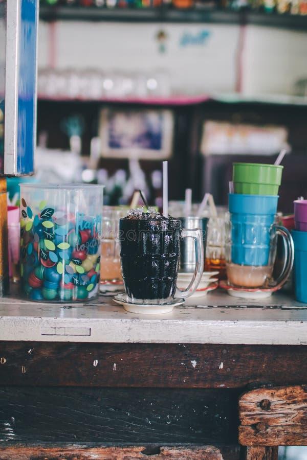 La bevanda locale ghiacciata tailandese della firma del caff? nero su fondo di legno ha chiamato il oliang fotografie stock libere da diritti