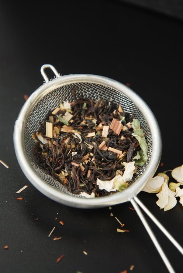 La bevanda sana del tè di erbe di Acaccia in ciotola ed il setaccio sopra fondo nero copiano lo spazio Bevanda sana, freddezza immagini stock