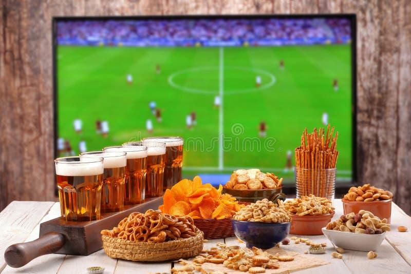 La bière et les casse-croûte ont placé sur le fond du match de football TV photographie stock