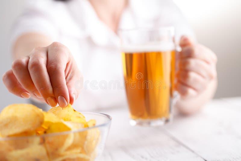 La bière potable et mangent de la nourriture industrielle, femelle à la maison égalisant photos libres de droits