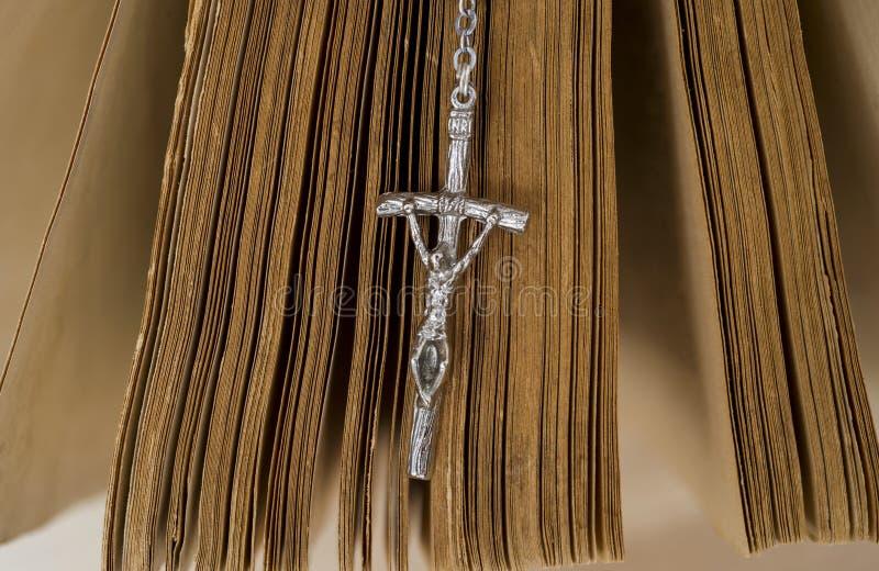 La bibbia santa con il rosario borda su fondo di legno fotografie stock