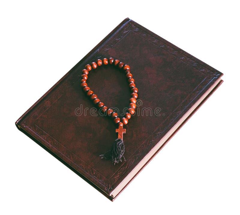La bible et le chapelet en bois d'isolement sur le fond blanc photos stock