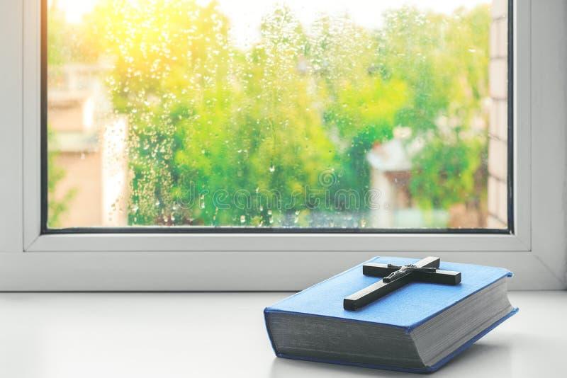 La biblia y la vieja cruz de madera en el alféizar Gotas de lluvia sobre el vidrio Tarde lluviosa La luz de la ventana Ut de la i foto de archivo libre de regalías