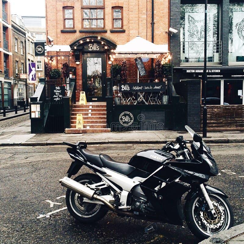 La bici blanco y negro del deporte de Yamah parqueó fuera de fachada de la tienda de las correas fotografía de archivo