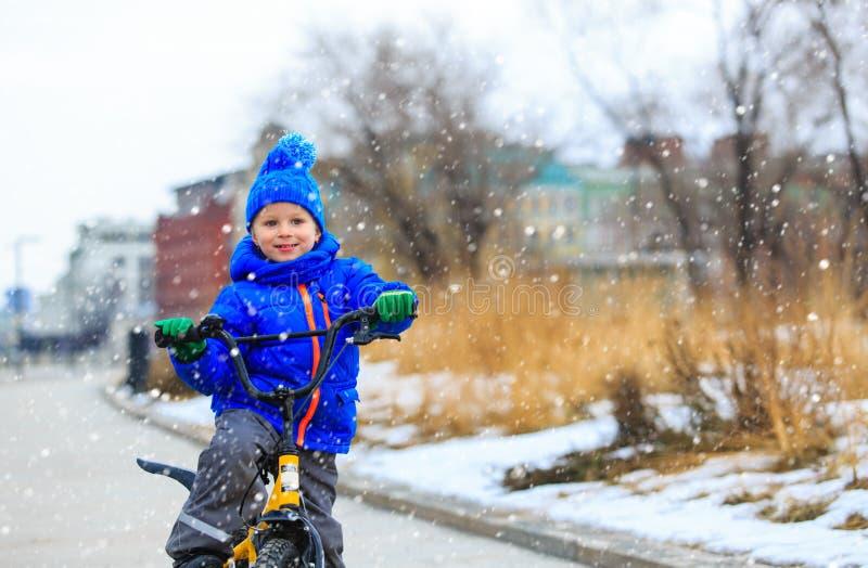 La bici linda en invierno, niños del montar a caballo del niño pequeño se divierte fotografía de archivo libre de regalías