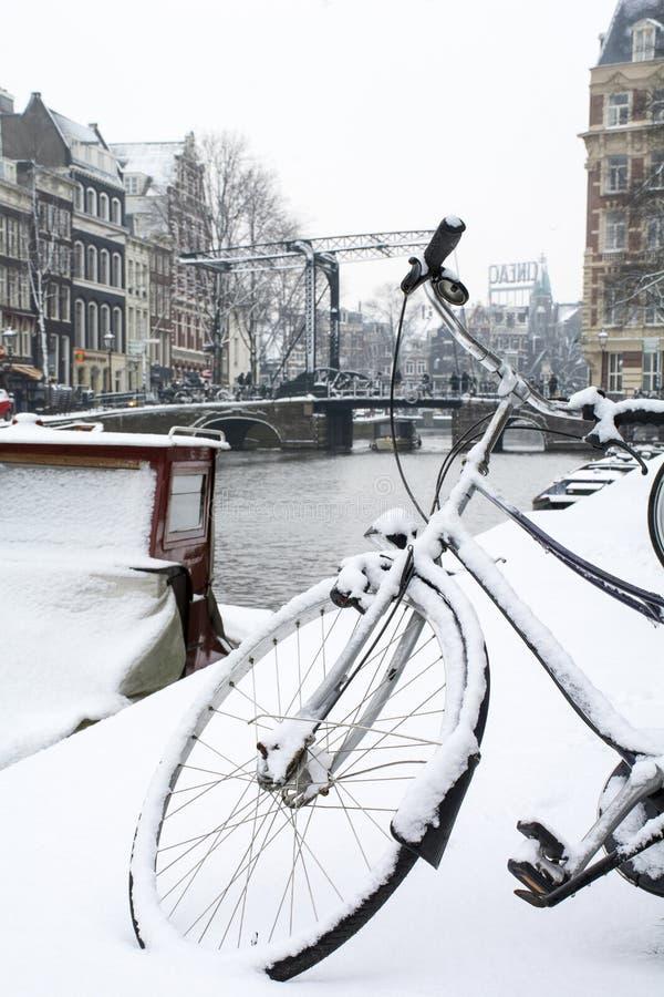 La bici negra rueda adentro nieve en Amsterdam con el canal y el puente fotos de archivo