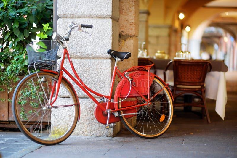 La bici roja enrrollada parqueó en una calle en la ciudad de Desenzano del Garda foto de archivo