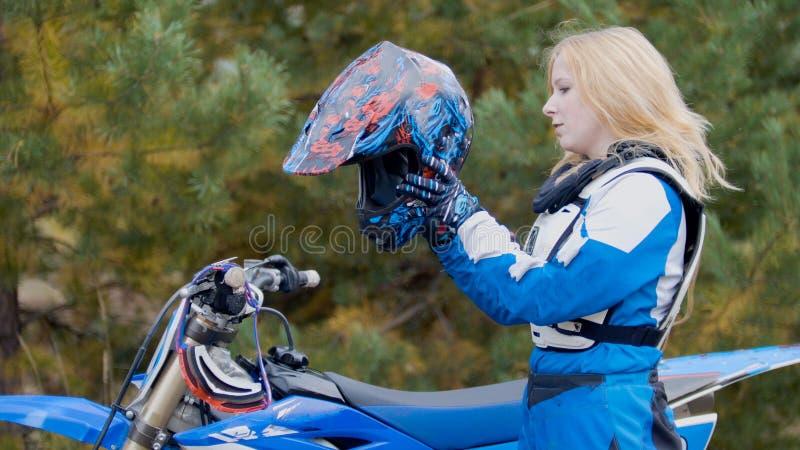 La bici rubia de la chica joven lleva un casco - el competir con cruzado del moto del MX - jinete en una motocicleta de la sucied foto de archivo