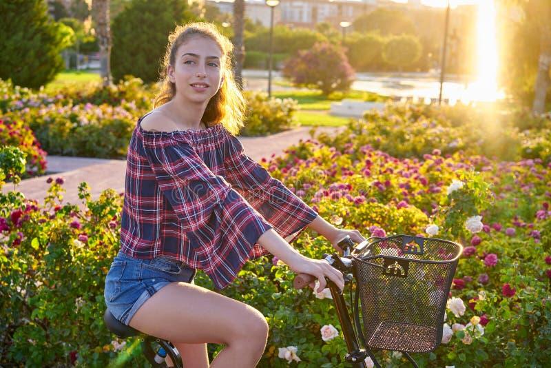 La bicicleta adolescente del montar a caballo de la muchacha en una ciudad florece el parque foto de archivo libre de regalías