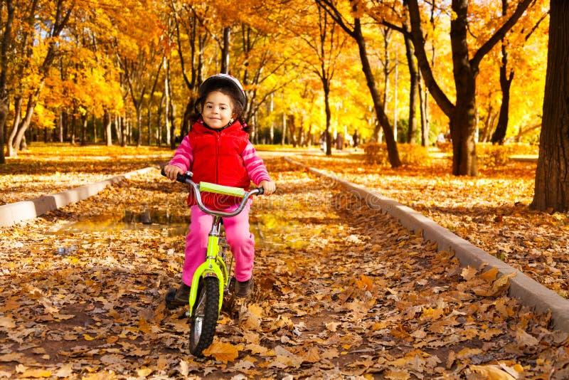 La bicicleta del montar a caballo de la muchacha el otoño montó imagen de archivo