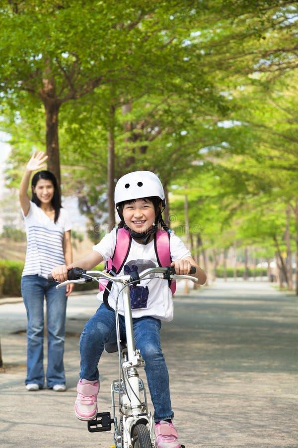 la bicicleta del montar a caballo de la niña va a la escuela fotografía de archivo