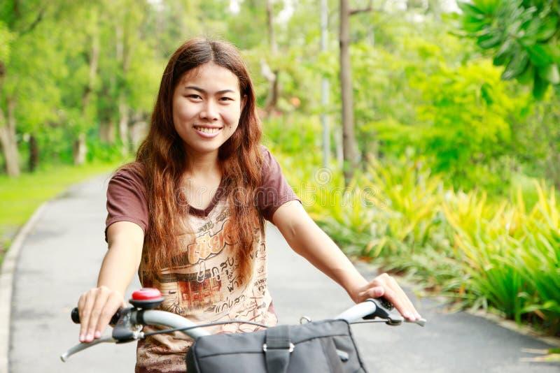 La bicicleta feliz joven del montar a caballo de la muchacha de Asia se relaja en parque imagen de archivo