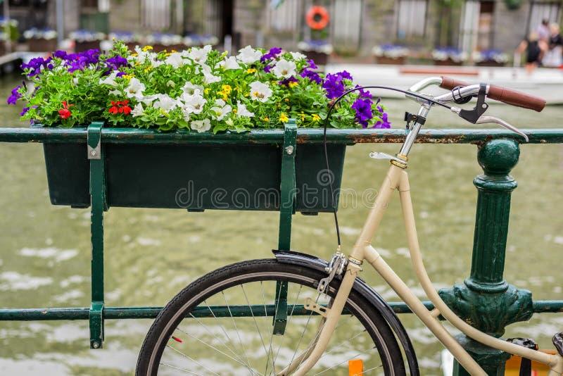 La bicicleta parqueó en el puente con las flores en Amsterdam Holanda imágenes de archivo libres de regalías