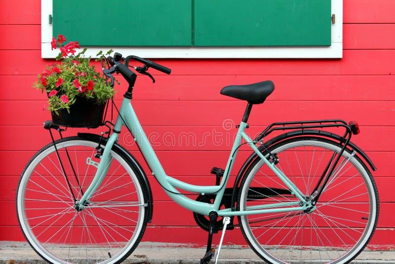 La bicicletta di Aquamarine davanti a una casa di legno rosso immagini stock libere da diritti