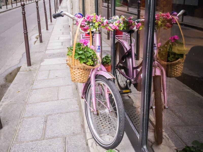 La bicicletta rosa decorata con i fiori pende contro una for Finestra con fiori disegno
