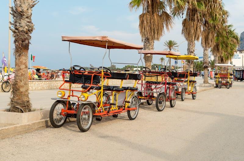 La bicyclette de pousse-pousse pour la location pour des touristes s'est garée près de la plage en San Vito Lo Capo image stock